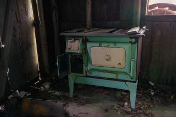 Old oven inside little cottage at Camp 18
